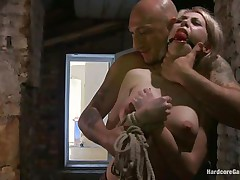 This sexy blond babe, Isabella Clark, gets abducted by a bald chap and taken to a quiet place. Her mouth is ball gagged and she is completely naked! The chap tied her on a bed and left her there. After a while, a chap comes in and begins teasing her with his cock and fucks her from behind